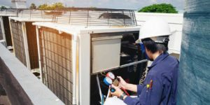 HVAC maintenance professional performing a system check on a rooftop HVAC system.jpg