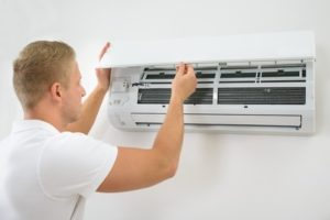 contractor working on an air conditioning wall unit