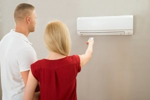young couple trying to get their brand new air conditioning unit to work