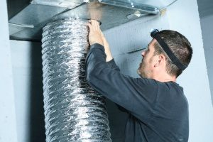 HVAC contractor performing duct work cleaning in a person's home
