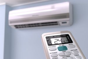 remote controlling a ductless mini-split air conditioner that is hanging on the wall