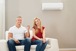 a couple relaxing next to their air conditioning unit that receives proper maintenance from a qualified HVAC contractor to improve their indoor air quality