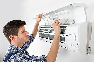 a professional HVAC contractor conducting regularly scheduled air conditioning maintenance within a Gaithersburg, MD home