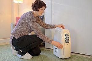 woman adjusting her brand new dehumidifier in order to lower the indoor humility level of her home and create optimal indoor air quality for her kids and dog