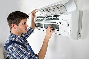 HVAC contractor inspecting air conditioning unit in Gaithersburg, MD to make sure it will work during the summer