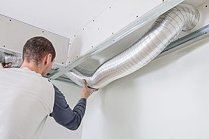 an HVAC contractor in the Gaithersubrg, MD area conducting an HVAC repair by fixing air ducts and repairing the unit itself
