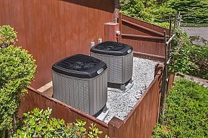 two adjacent outdoor AC units that will need preventive HVAC maintenance in order to function during the summer