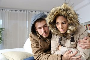 couple sitting in coats inside their home because they need a heating repair