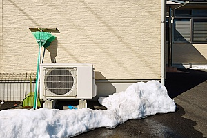 a heating system that was covered in snow during the winter months and needs repair from HVAC contractors