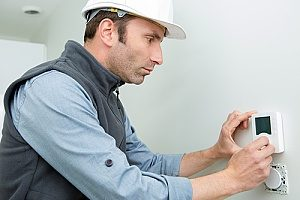 a Gaithersburg, MD HVAC contractor who is installing a new thermostat after conducting a full heating system replacement in a large modern home