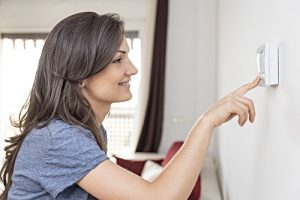 woman homeowner happily adjusting a thermostat after a successful furnace installation