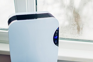 a dehumidifier that is being adjusted to the ideal indoor humidity in winter