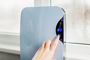 a woman using a dehumidifier to combat high humidity levels