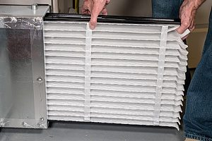 an air filter being replaced for a high efficiency condensing furnace