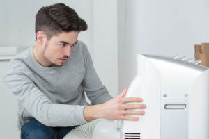 a man configuring the settings on a dehumidifier