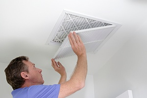man changing the air filter of his central air conditioner