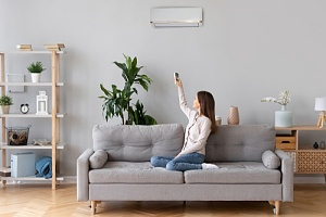 woman on couch using remote to control central air conditioning