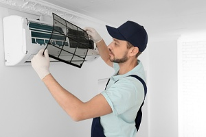 a man learning to check the freon in a home air conditioner