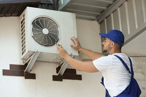 a man looking at a split system air conditioner on a home