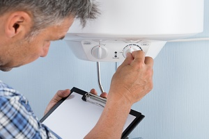 man checking the thermostat on the home heating system