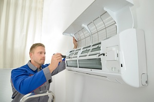 man installing a ductless vs. central air system