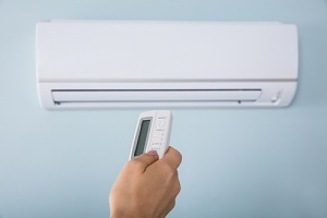 someone controlling a ductless vs. central air conditioner system
