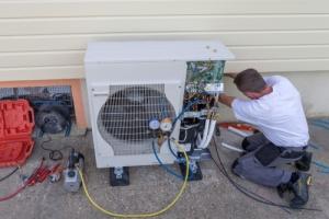 man installing a heat pump before the winter months