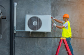 a contractor replacing a central AC unit on the site of a building