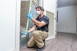 HVAC professional changing the filter of an ac unit inside of a home