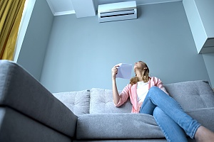 a woman staring up at her broken dehumidifier that needs to be repaired by an HVAC professional