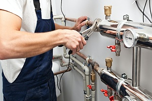 arms of an HVAC professional who is repairing a heating system in a residential home