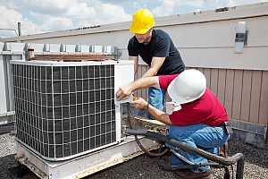 two HVAC contractors installing an ac unit on a roof top