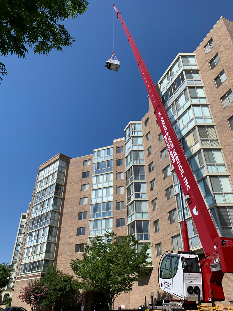 Presidential crane lifting commercial HVAC unit to roof of condominiums