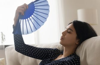 Woman fanning herself due to broken air conditioning